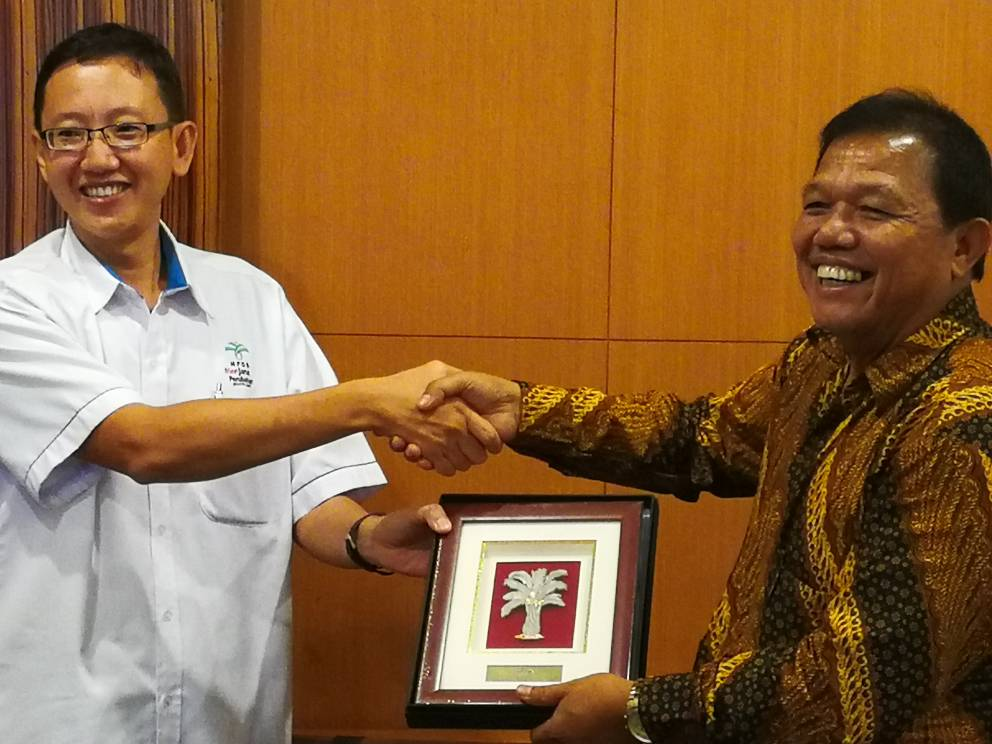 Dr Harrison Lau receiving a memento from PT Pertamina Patra Niaga's Operations Director Gema Iriandus Pahalawan.