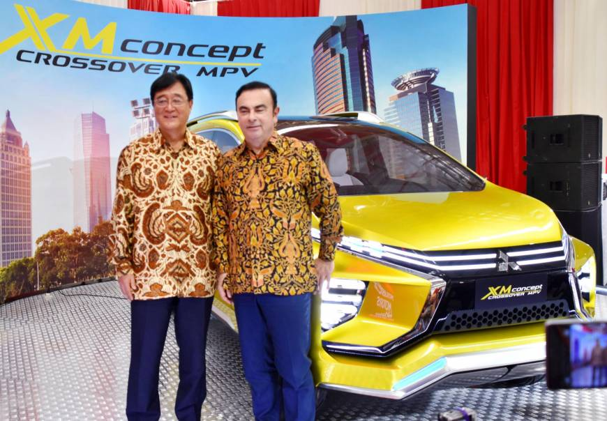 Renault-Nissan Alliance's chairman and chief executive officer Carlos Ghosn together with Mitsubishi Motors Corporation's chief executive officer Osamu Masuko, posing next to the new compact MPV.